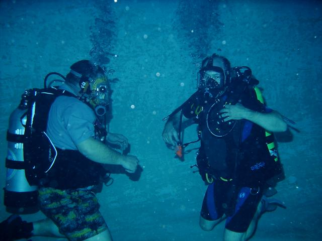 Two divers practicing sharing air while underwater